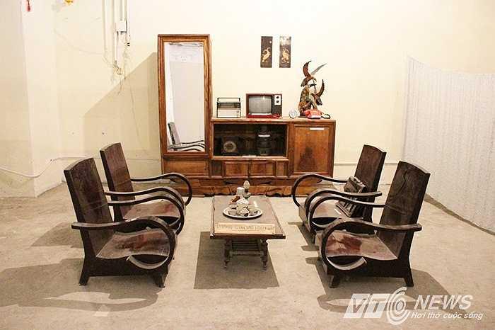 Không gian mô phỏng phòng khách của một gia đình thời bao cấp với bộ bàn ghế salon gỗ, tủ lệch tráng gương, bộ ấm chén, đèn dầu.