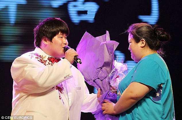 Yuanjun hát và tặng hoa mẹ trong một chương trình ca nhạc.