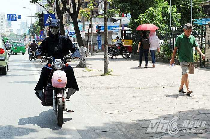 Người thì mặc áo chống nắng, người thì dùng ô để chống chọi với cái nắng gay gắt của trưa hè.