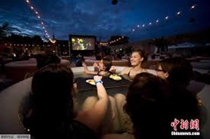 Bồn tắm được đặt trên bãi rộng, các màn hình chiếu phim lớn đặt cách hàng mét với những bộ phim nổi tiếng