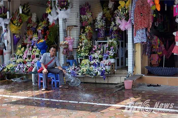 Một người đàn ông bán hoa trên đường Kim Mã phải xịt nước ra khu vực vỉa hè trước nhà để làm mát.