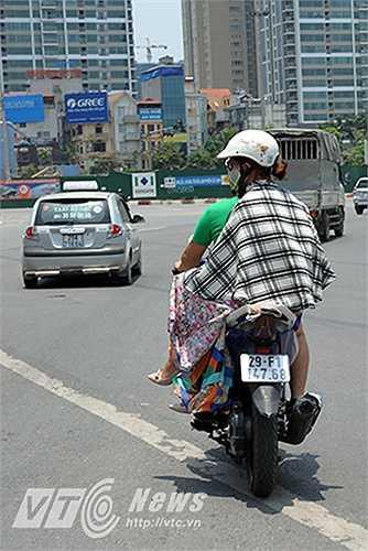 Thậm chí có người đi xe máy còn phải khoác chăn để làm áo chống nắng.