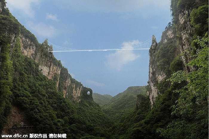Hình ảnh ấn tượng về cây cầu kính nối giữa hai ngọn núi sừng sững giữa phong cảnh núi non điệp trùng.
