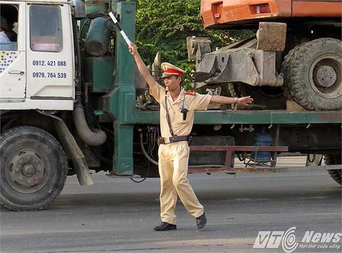 Mặc cho thời tiết nắng nóng, ngột ngạt, thượng úy Phạm Văn Hạnh - CSGT đội 2 vẫn đang căng mình làm nhiệm vụ điều tiết, phân làn giao thông.