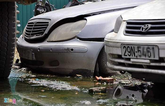 Một chiếc Mercedes đời cũ đắt tiền ngập bùn trong bãi giữ phương tiện vi phạm. Bốn bánh xe này đã bị xì hơi, ba-đờ-sốc bong tróc.