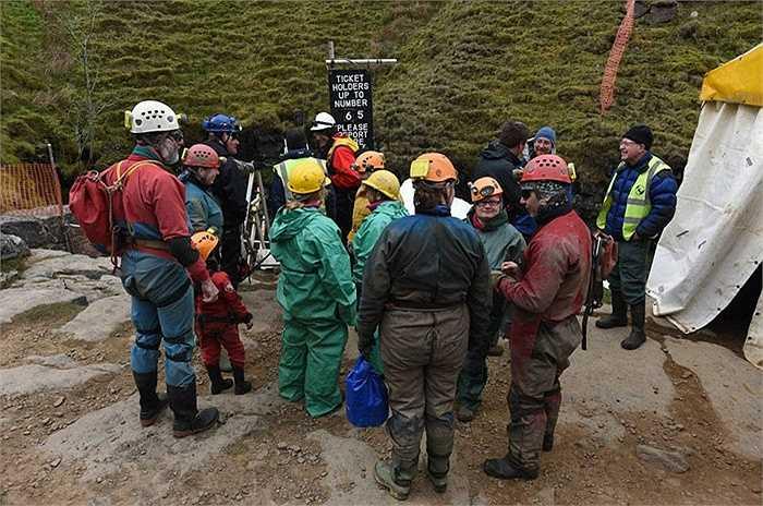 Những người thám hiểm mặc đồ bảo hộ chuẩn bị đu xuống hang.