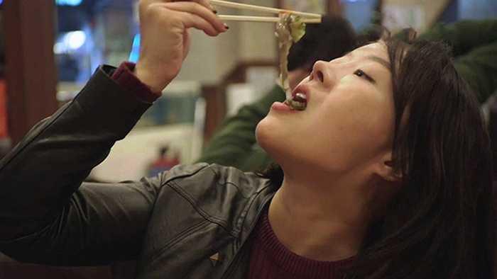 Một thực khách thưởng thức món bạch tuộc sống tại nhà hàng.