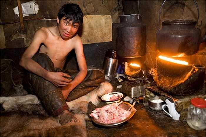 Một thanh niên bộ tộc Nenets đang chuẩn bị bữa tối cho gia đình bằng bữa thịt sống thịnh soạn.