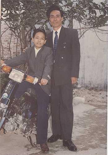 Phan Anh chụp ảnh cùng bố khi gia đình mua được chiếc xe máy còn anh được bố mẹ 'tậu' cho bộ vest mới. Dù trang phục rộng thùng thình nhưng được mọi người khen mặc ra dáng người lớn nên cậu bé Phan Anh khi đó rất thích. Ảnh: NVCC