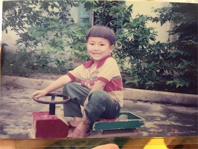 Cậu bé Công Tố với mái tóc ngang 'ngố tàu' tạo dáng bên chiếc xe tự chế của bố. Ảnh: Nhân vật cung cấp