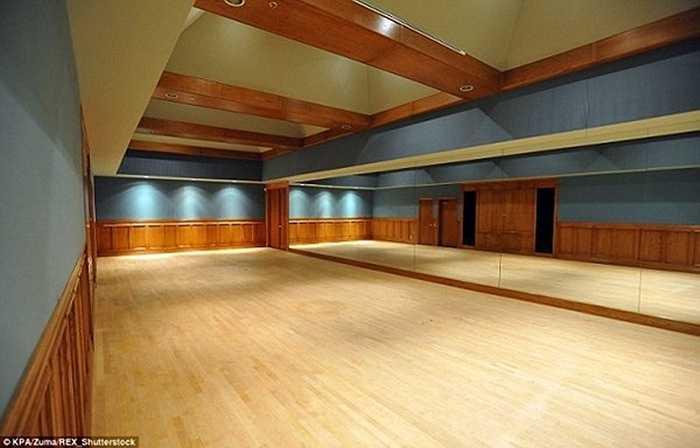 Phía sau là một phòng tập rộng rãi với sàn gỗ và tường có gương.