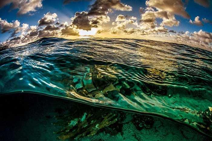 Dòng nước với sóng bập bềnh, nền trời nhiều đám mây đủ màu hòa trong màu xanh của nước biển