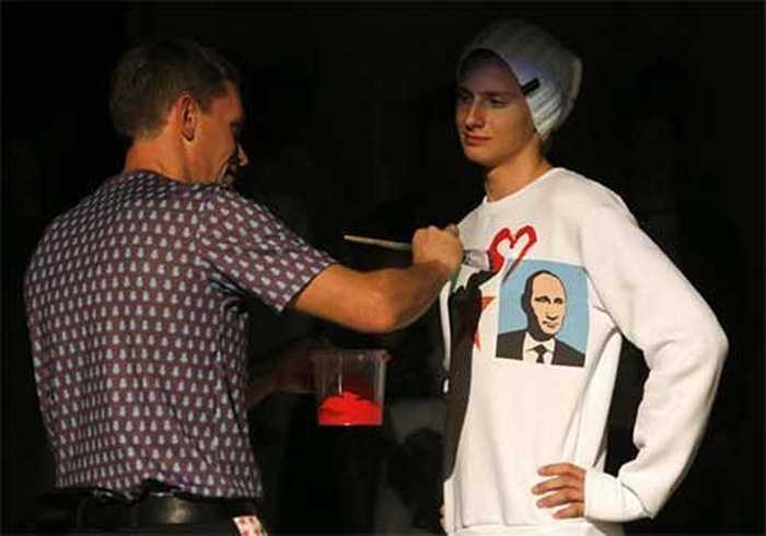 Họa sĩ Alexey Sergienko (trái) đang vẽ hình trái tim lên chiếc áo in hình ông Putin tại buổi giới thiệu nhãn hàng thời trang Homeland, được tổ chức vào ngày sinh nhật lần thứ 62 của Tổng thống Nga