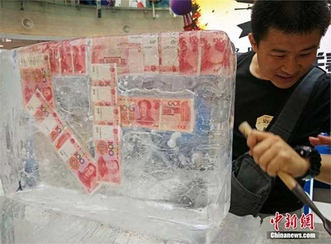 Một vị khách may mắn đang cố gắng lấy tờ tiền 100 nhân dân tệ. Số tiền được đông đá lên đến khoảng 2.000 nhân dân tệ