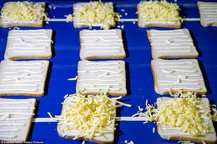 Sau khi đã được quét sốt mayonaise, các bánh mỳ được phủ thêm lớp pho mát bào nhỏ