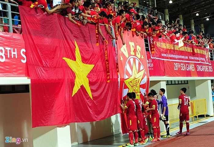 Kết thúc trận đấu, các tuyển thủ ký lên lá quốc kỳ lớn của CĐV
