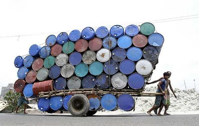 Người đàn ông kéo chiếc xe chất đầy thùng phuy