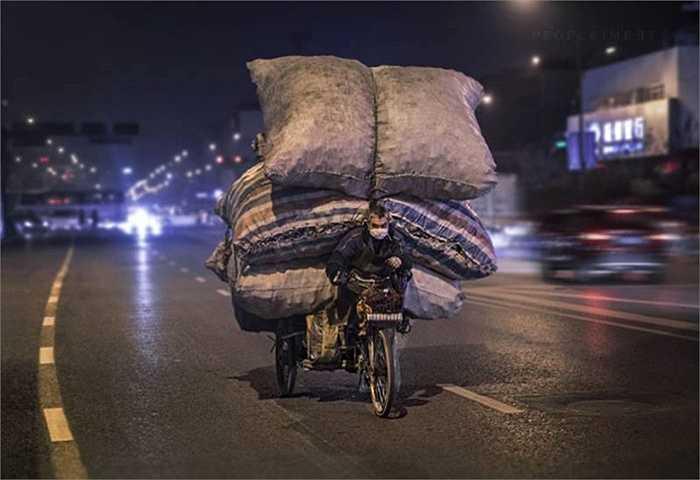 Người lao động với xe đầy hàng trong đêm