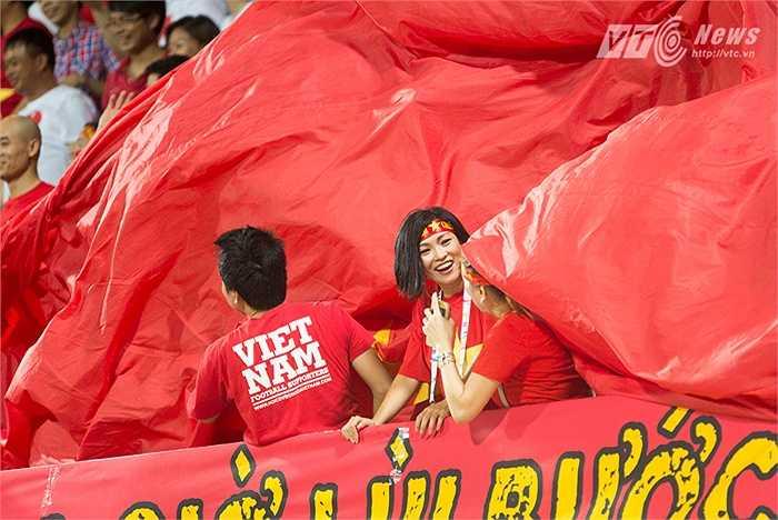 Nữ ca sĩ Phương Thanh cổ vũ hết mình cho U23 Việt Nam. Hình ảnh Phương Thanh dưới đại kỳ. (Ảnh: Hoàng Thịnh)