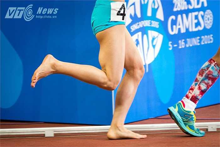 Với đôi chân trần Phạm Thị Huệ vẫn băng băng trên đường chạy trong khi ngay phía trước cô, VĐV của Thái Lan có đôi chân đầy 'màu sắc'. (Ảnh: Hải Thịnh)