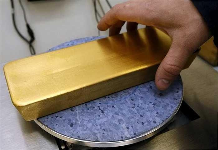 Một công nhân cân trọng lượng của thỏi vàng 99,99% trước khi chuyển nó sang máy chạm khắc.