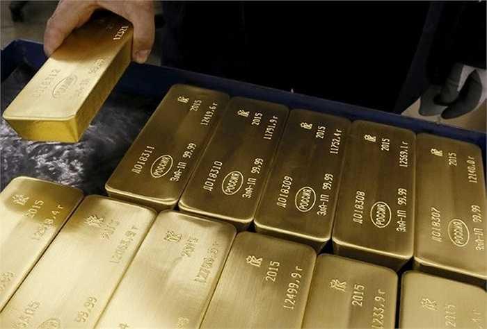 Công nhân xếp những thỏi vàng đã khắc thông tin vào thùng hàng trên xe đẩy. Theo Reuters, công ty Krastsvetmet đặt mục tiêu tăng sản lượng sản xuất vàng thỏi đến 55% trước năm 2025.