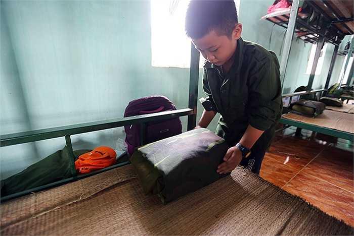 Minh Quân, 9 tuổi , trường tiểu học Vân Yên đã học được cách gập chăn màn vuông vức hình chiếc bánh trưng