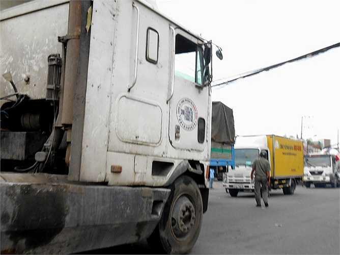 Một bảo vệ dân phố lọt thỏm trước các xe container, xe tải khi xuống đường điều tiết giao thông.