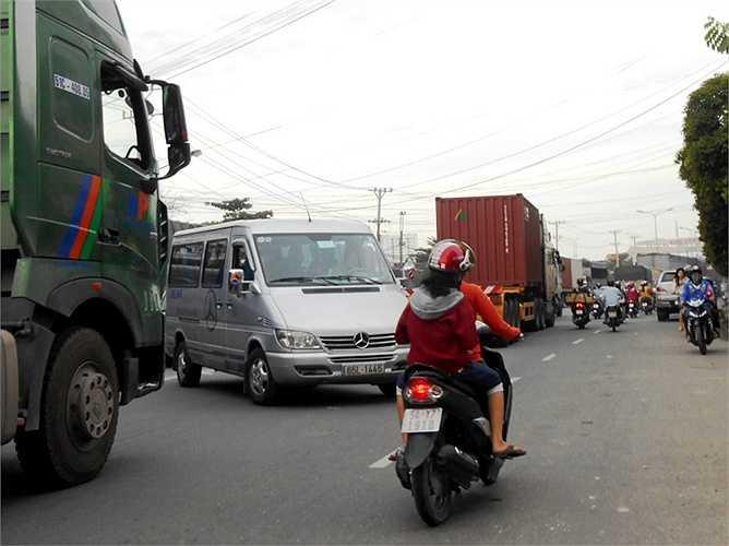 Một ô tô cắt mặt container chen ngang qua đường.