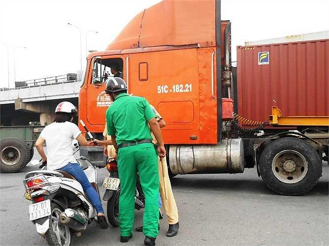 Một cô gái hốt hoảng té ngã khi phát hiện xe container di chuyển trước mặt.