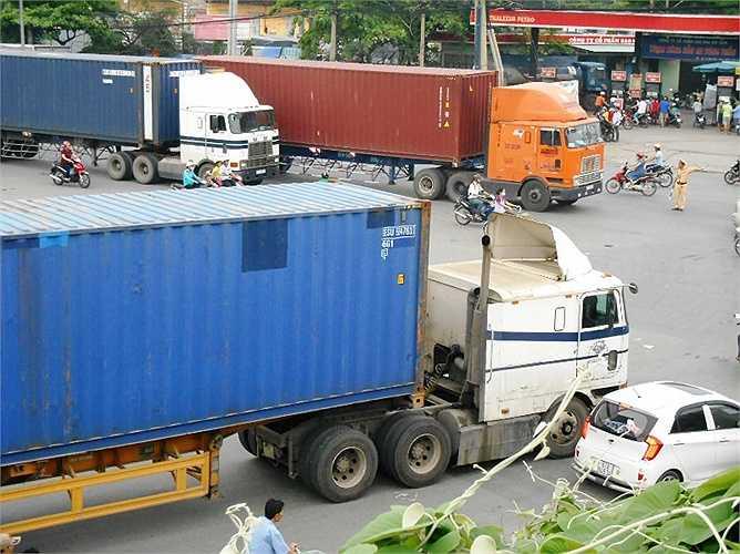 Lực lượng CSGT vất vả điều tiết giao thông khi nhiều xe container lăn bánh cùng lúc.