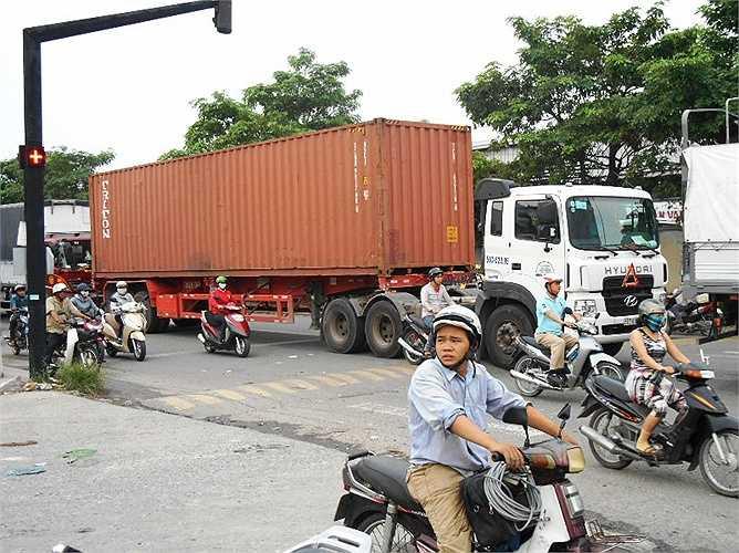 Xe máy di chuyển sát container nguy cơ xảy ra tai nạn giao thông lớn.