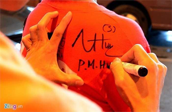 Hậu vệ Phạm Mạnh Hùng ký lên áo người hâm mộ.