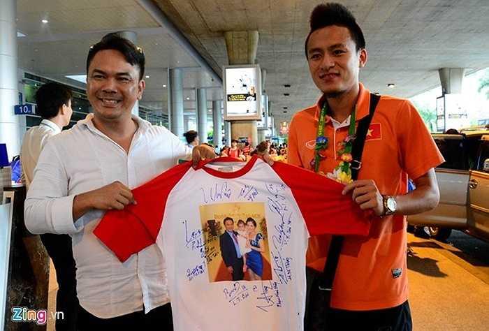 Anh Nam, một CĐV TP HCM sưu tập chữ ký của ban huấn luyện, các cầu thủ U23 Việt Nam trên chiếc áo in hình gia đình.