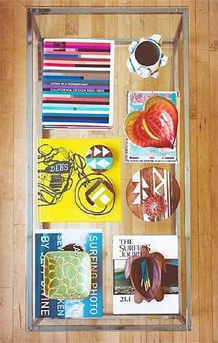Trang trí bằng sách  Một cách hay để biến phòng khách thành phòng đọc là dùng chính những cuốn sách ưa thích của bạn để trang trí cho chiếc bàn uống nước. Chiếc bàn kính hai tầng đã trở nên sống động hơn nhờ giá sách đầy màu sắc xếp ở tầng dưới.