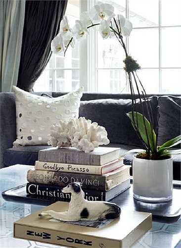 Dùng tượng sứ và hoa  Bình phong lan trắng muốt và những bức tượng sứ đã tăng vẻ độc đáo cho chiếc bàn thủy tinh.