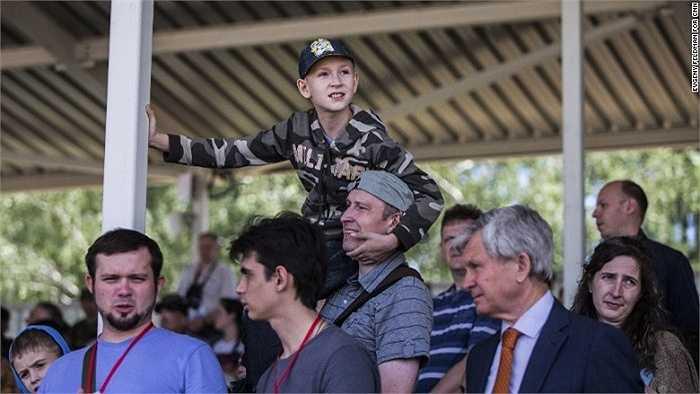 Cậu bé mặc bộ đồ quân sự thích thú xem xe tăng trình diễn