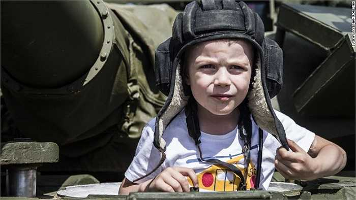 Cậu bé thích thú khi được ngồi trên chiếc xe tăng