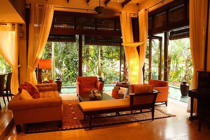 Phòng khách thoáng đãng, giao hòa với thiên nhiên nhưng cũng vô cùng ấm áp nhờ vào nội thất gam màu nóng và ánh đèn vàng.