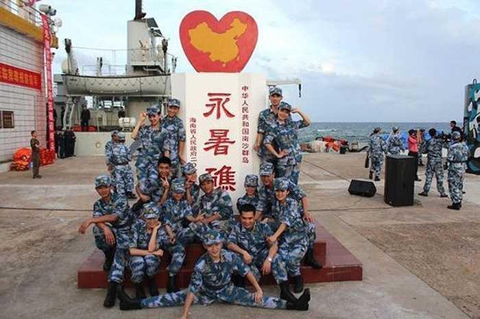 Họ tạo dáng chụp ảnh trên đá Chữ Thập đang chiếm đóng trái phép của Việt Nam