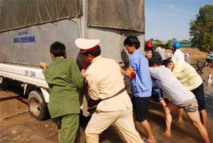 Thêm một hình ảnh nữa về thái độ tận tâm của cảnh sát giao thông hợp sức cùng người dân cứu giúp một xe tải bị sa lầy trong mưa lũ.