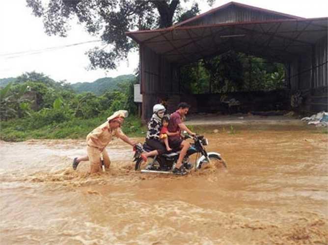 Hình ảnh hai CSGT lăn xả giữa dòng nước chảy xiết để đẩy xe, giúp dân vượt qua đoạn đường nguy hiểm được lan truyền trên mạng vào tháng 8/2012 từng khiến cư dân mạng cảm kích.