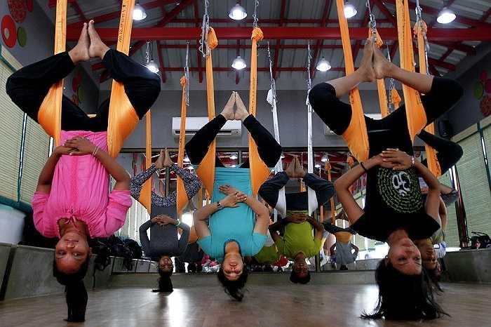 Một số người tập yoga trong tư thế treo ngược, lơ lửng ở Ahmadabad, Ấn Độ