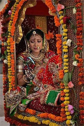 Hình ảnh cô dâu trong ngày cưới với vô vàn trang sức đeo nặng trĩu trên người. Đây là của hồi môn nhà bố mẹ đẻ trao cho con gái trước khi về nhà chồng. Các loại vàng, bạc, ngọc trai giúp cho cô dâu trở nên rực rỡ. Ngoài ra, chiếc kiệu nhiều màu sắc được trang trí bằng hoa tươi.