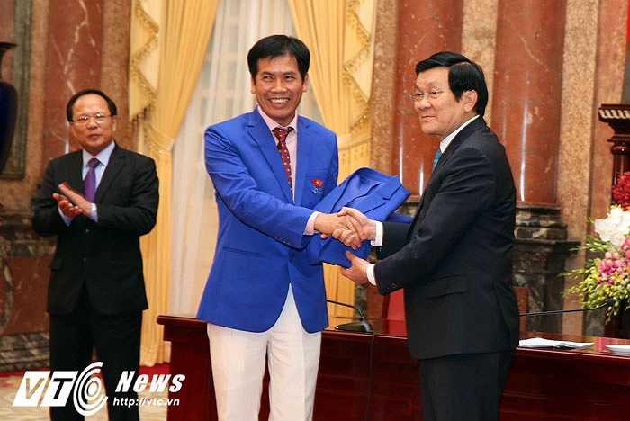 Sau cuộc gặp, ông Trần Đức Phấn, trưởng đoàn TTVN tại SEA Games đã tặng Chủ tịch nước chiếc áo lưu niệm của đoàn TTVN. (Ảnh: Quang Minh)