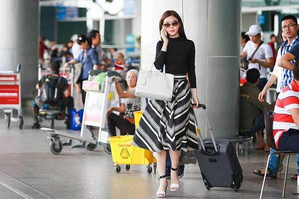Mỹ nhân sinh năm 1991 diện trang phục kín đáo với áo thun mix cùng chân váy kẻ sọc, cô đeo túi xách Prada làm điểm nhấn.