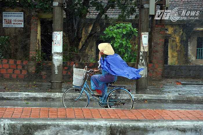 Người dân đi lại khó khăn dưới sức gió mạnh của bão số 1.  Thực hiện: Chiến Linh