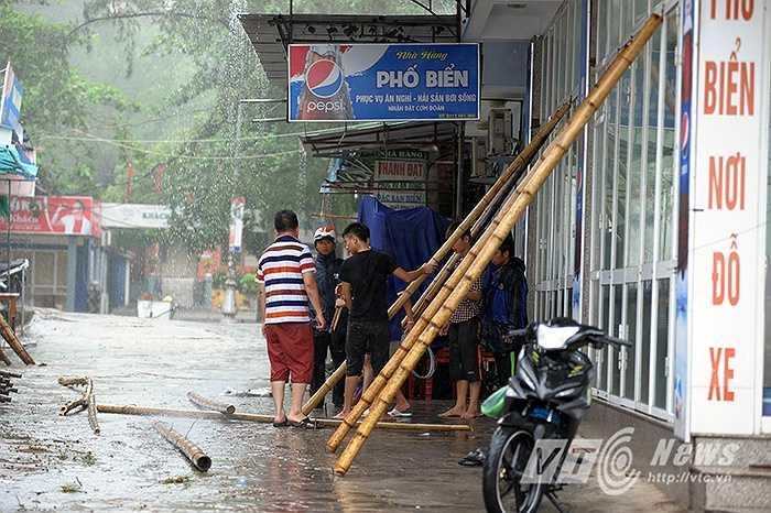 Người dân vẫn cố gắng chằng chéo hàng quán dưới trời mưa lớn, gió giật mạnh.