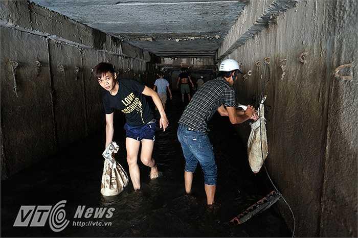 Chỉ trong một loáng, hàng bao tải cá đã được người dân bắt và đưa ra ngoài.