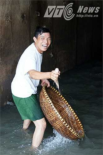 """Bác Lập (Mai Động, Hà Nội) cho biết: """"Sáng nay tôi đi làm về thấy người dân đang bắt cá ở đây nên tôi cũng nhảy xuống bắt cùng, vui lắm."""""""